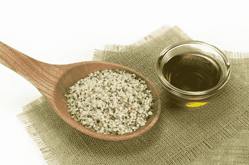Wooden spoon with hemp seeds and glass bowl with Elixinol hemp seed oil